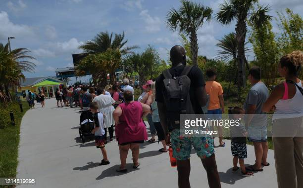 People wait in a queue to enter Island H2O Live water park as the attraction becomes the only major water park in the Orlando area to reopen for...
