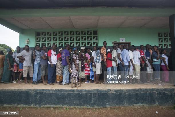 People wait in a queue to vote in the general election at Sr Kathleen McGuire Memorial Catholic school in Monrovia Liberia on October 10 2017