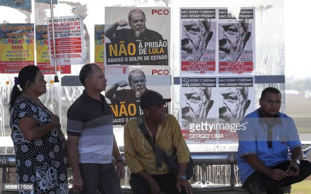 People wait in Brasilia on January 22 2018 at a bus stop covered in posters in support of Brazilian former President Luiz Inacio Lula de Silva...