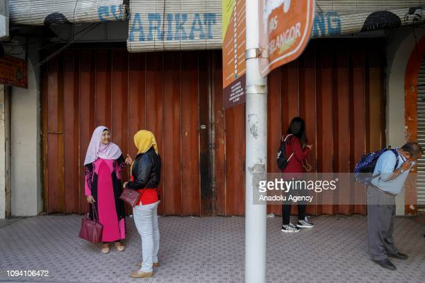 People wait in front of a closed shop during Chinese New Year celebration in Kuala Lumpur Malaysia on February 5 2019 Malaysian government set...
