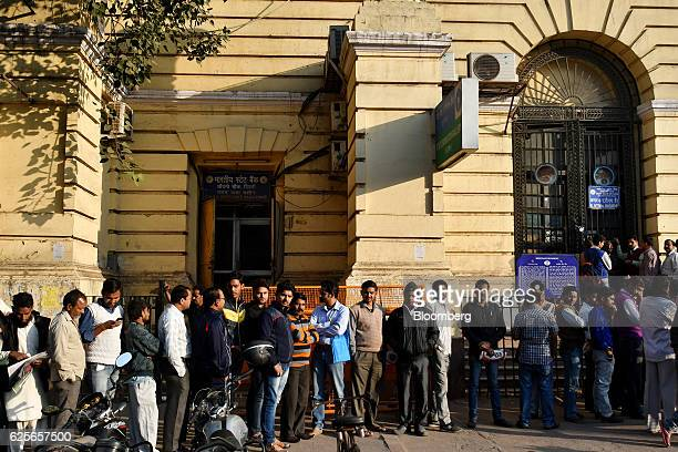 People wait in in line for a State Bank of India branch to open in Delhi India on Friday Nov 25 2016 India's government is grappling with a furor...