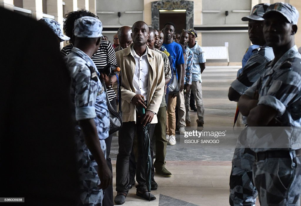 People wait in line as soldiers control people prior to enter the courtroom of Abidjan during Ivory Coast's former first lady trial on May 31, 2016. Simone Gbagbo goes on trial for crimes against humanity in what many see as a litmus case for justice in the West African country. The hearings into the 66-year-old's role in post-election carnage in 2010 is expected to last a month with 32 witnesses testifying. / AFP / ISSOUF