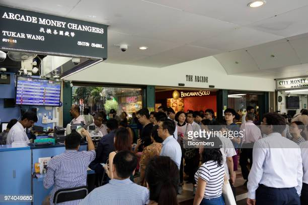 People wait in line at a currency exchange in the central business district of Singapore on Wednesday June 13 2018 Tourism as well as the consumer...
