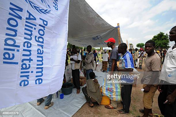 People wait in line at a food aid distribution point of the UN World Food Programme near a camp for internally displaced persons in Bangui on...