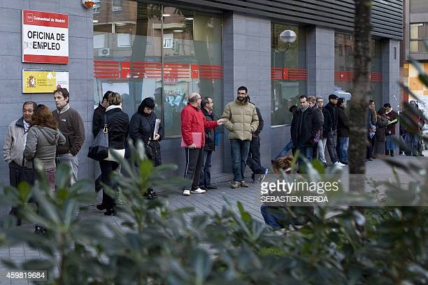 People wait in line at a government employment office on Paseo de las Acacias in Madrid on December 2 2014 Spain's jobless queue shrank in November...