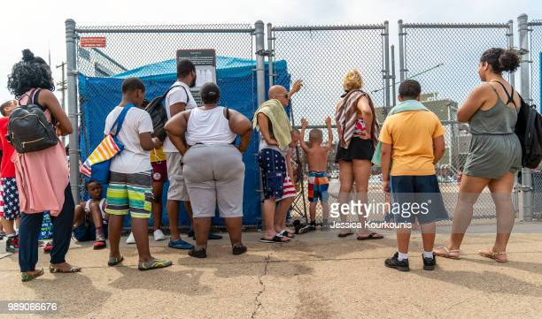 People wait in line at a public pool that is filled to capacity during a heatwave on July 1 2018 in Philadelphia Pennsylvania An excessive heat...