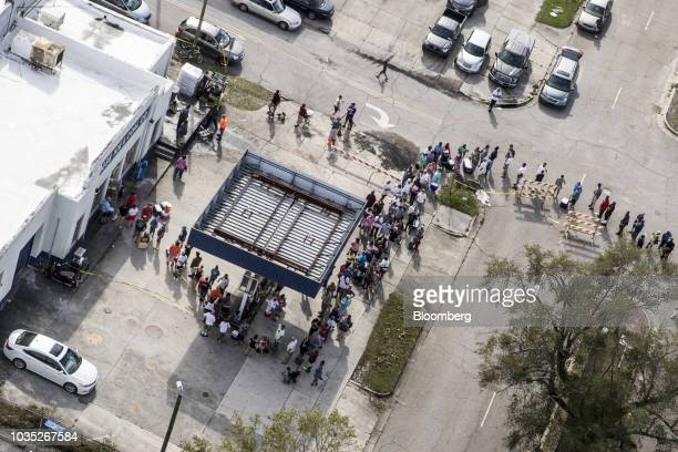 People wait in line at a Rose Ice Coal Co store in this aerial photograph taken after Hurricane Florence hit in Wilmington North Carolina US on...