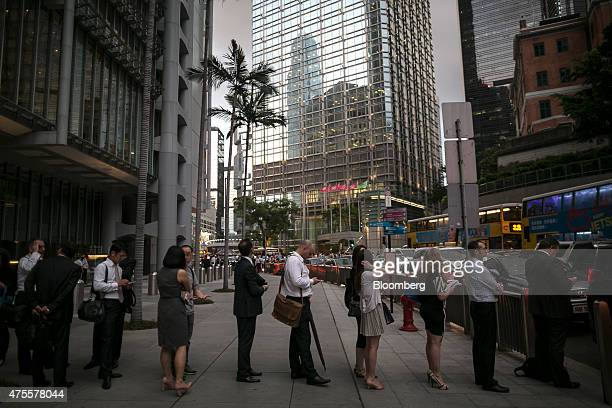 People wait in line at a taxi rank near the Cheung Kong Center building center in the Central district of Hong Kong China on Thursday May 28 2015...