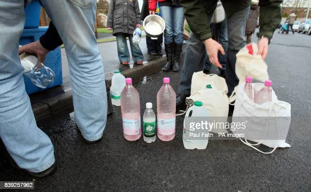 People wait in line at Avoniel leisure centre in east Belfast with empty bottles to get drinking water as tens of thousands of homes and businesses...