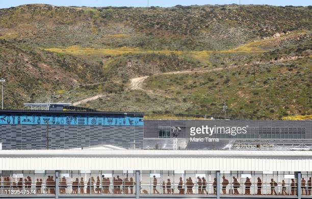 People wait in line at the El Chapparal port of entry on their way to enter the United States on March 31 2019 in Tijuana Mexico US President Donald...