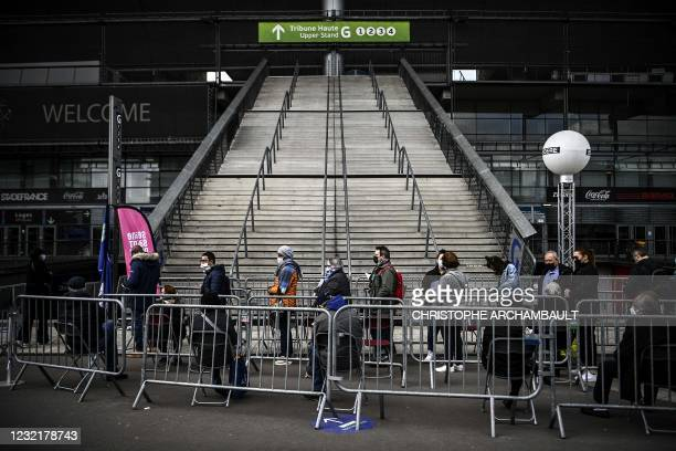 People wait in line before beeing vaccinated against Covid-19 at a vaccination centre set in the Stade de France in Saint-Denis, a northern Paris...