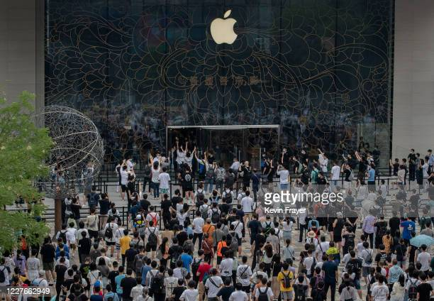 People wait in line following social distancing rules as others enter during the official opening of the new Apple Store in the Sanlitun shopping...