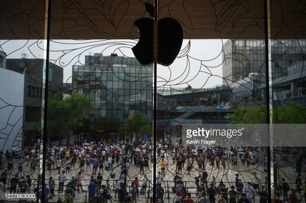 People wait in line following social distancing rules at the official opening of the new Apple Store in the Sanlitun shopping area on July 17 2020 in...