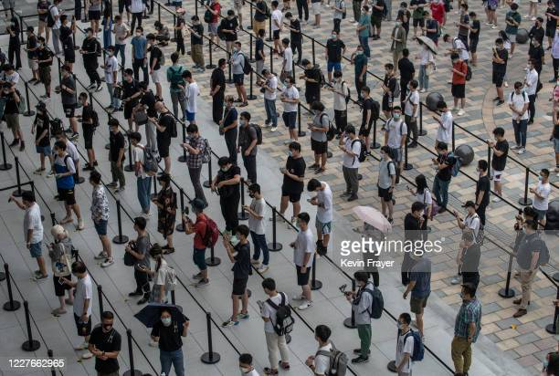 People wait in line following social distancing rules before the official opening of the new Apple Store in the Sanlitun shopping area on July 17...