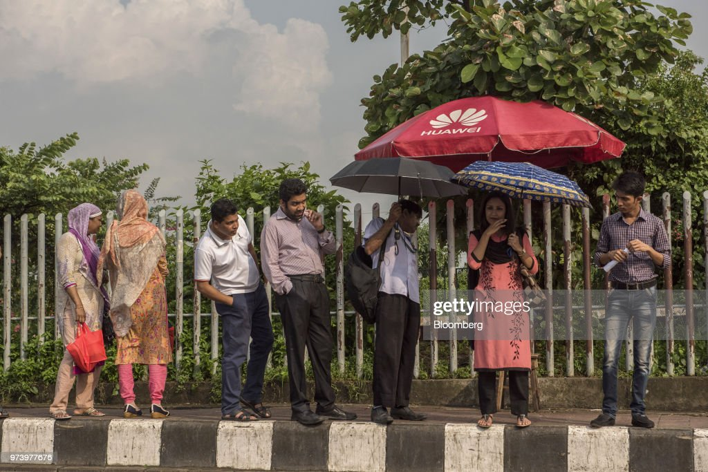 People wait in line for a bus in Dhaka, Bangladesh, on Wednesday, June 6, 2018. The Bangladesh economy will expand 6.9% this financial year and 6.8% in 2019, according to asurveyconducted by Bloomberg News. Photographer: Ismail Ferdous/Bloomberg via Getty Images