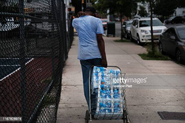People wait in line for bottled water at a recreation center on August 13 2019 in Newark New Jersey Residents of Newark the largest city in New...