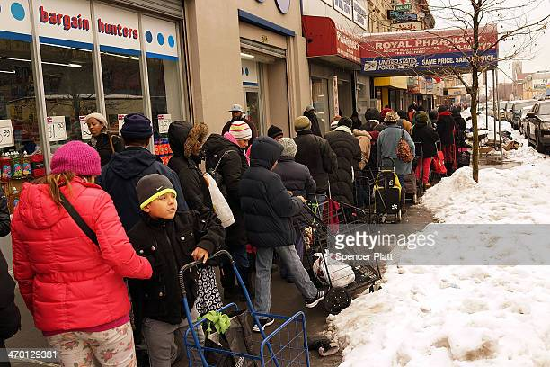 People wait in line for CAMBA's Beyond Hunger Emergency Food Pantry on February 18 2014 in the Brooklyn borough of New York City The nonprofit agency...