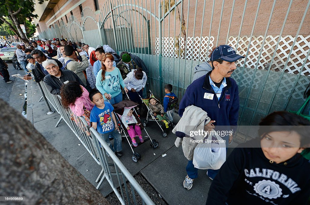 People wait in line for dinner on Good Friday during the Skid Row Easter event at the Los Angeles Mission on March 29, 2013 in Los Angeles, California. Volunteers, celebrities and nurses distributed more than 1000 Easter baskets to children and provided 3,500 hot meals, 2,000 pairs of shoes and and podiatric care to the homeless of Skid Row.
