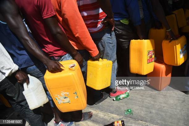 TOPSHOT People wait in line for gas in the commune of Petion Ville in the Haitian Capital PortauPrince on February 17 2019 The government presented a...