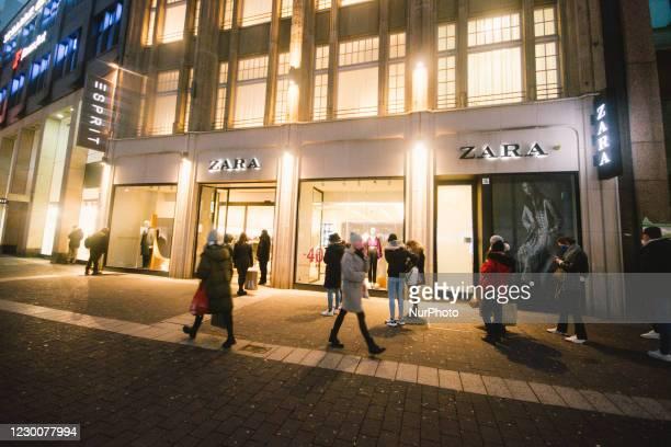 People wait in line for getting into zara retailer shop in duesseldorf