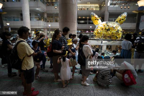 People wait in line in front of balloons in the shape of the Pikachu a character from Pokemon series game titles at a shopping mall during the...