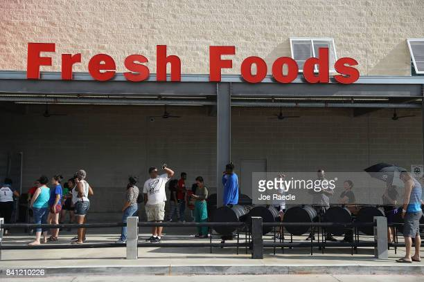People wait in line in hopes of buying water at a grocery store after the water supply to the city of Beaumont was shut down after Hurricane Harvey...