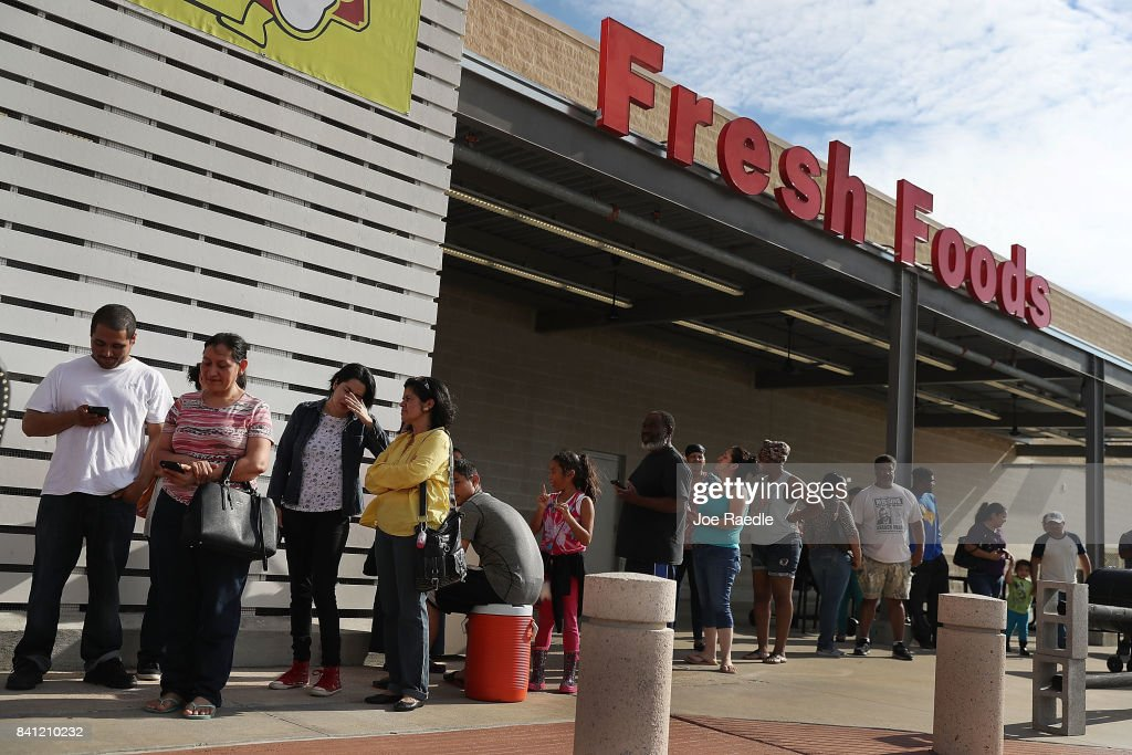 People wait in line in hopes of buying water at a grocery store after the water supply to the city of Beaumont was shut down after Hurricane Harvey passed through on August 31, 2017 in Beaumont, Texas. Harvey, which made landfall north of Corpus Christi August 25, has dumped more than 50 inches of rain in some areas in and around Houston.