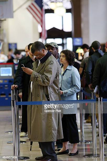 People wait in line in the James A Farley post office in Manhattan which is staying open until midnight today on that last day to file taxes on April...