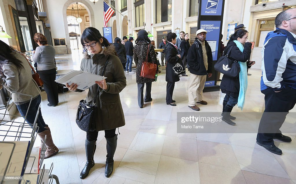 People wait in line (R) inside the James A. Farley post office building April 15, 2013 in the Manhattan borough of New York City. With the U.S. tax deadline of midnight April 15 rapidly approaching, last-minute filers are filling up the nation's post offices.