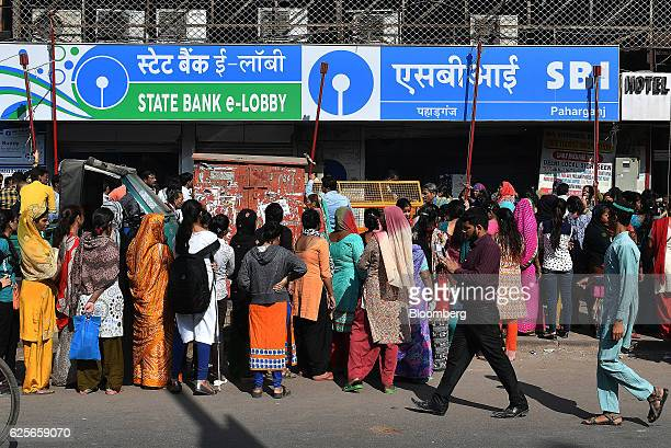 People wait in line outside a State Bank of India branch in Delhi India on Friday Nov 25 2016 India's government is grappling with a furor over a...