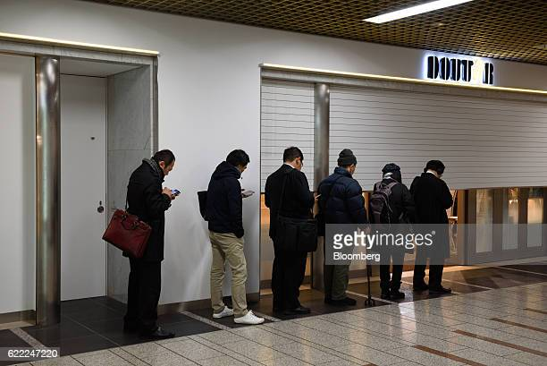 People wait in line outside a store operated by Doutor Coffee Co before it opens in Kawasaki Kanagawa Prefecture Japan on Thursday Nov 10 2016...
