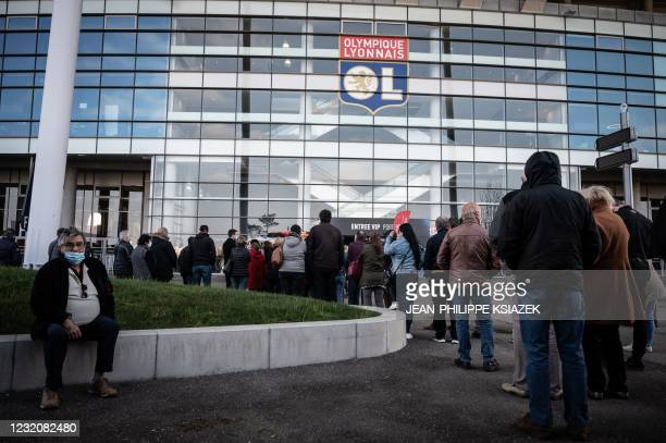 People wait in line outside as they arrive to be vaccinated against Covid-19 on the opening day of a mass vaccination centre set up in the OL Group's...