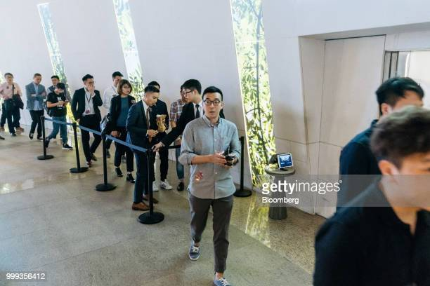 People wait in line outside the sales office for the Victoria Harbour residential project developed by Sun Hung Kai Properties Ltd in Hong Kong China...