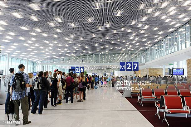 People wait in line prior to taking on board at the new boarding hall of Terminal 2E S4 at RoissyCharlesdeGaulle airport in RoissyenFrance northern...