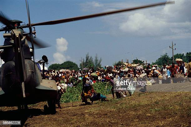 People wait in line to be rescued and taken by helicopter to Chibuto.