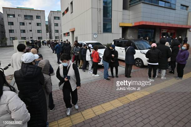 People wait in line to buy face masks from a post office near the Daegu branch of the Shincheonji Church of Jesus in Daegu on February 27, 2020. -...