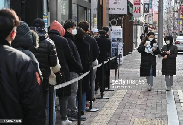 People wait in line to buy face masks from a store at the Dongseongro shopping district in Daegu on February 27, 2020. - South Korea reported 334 new...
