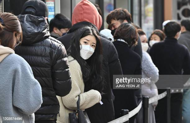 People wait in line to buy face masks in front of a store at Dongseongro shopping district in Daegu on February 27, 2020. - South Korea reported 334...