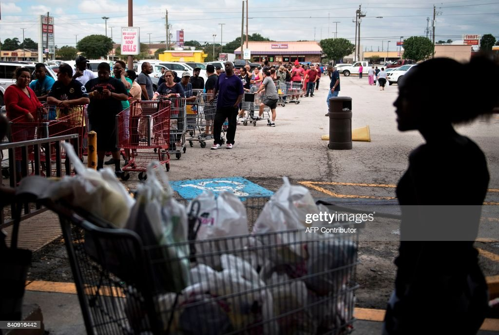TOPSHOT - People wait in line to buy groceries at a Food Town during the aftermath of Hurricane Harvey on August 30, 2017 in Houston, Texas. Monster storm Harvey made landfall again Wednesday in Louisiana, evoking painful memories of Hurricane Katrina's deadly strike 12 years ago, as time was running out in Texas to find survivors in the raging floodwaters. / AFP PHOTO / Brendan Smialowski