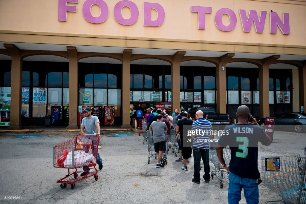 People wait in line to buy groceries at a Food Town during the aftermath of Hurricane Harvey on August 30, 2017 in Houston, Texas. Monster storm Harvey made landfall again Wednesday in Louisiana, evoking painful memories of Hurricane Katrina's deadly strike 12 years ago, as time was running out in Texas to find survivors in the raging floodwaters. / AFP PHOTO / Brendan Smialowski