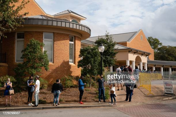 People wait in line to cast their ballots at an early voting location in the Smyrna Community Center on October 24 in Smyrna Georgia Neighbors and...