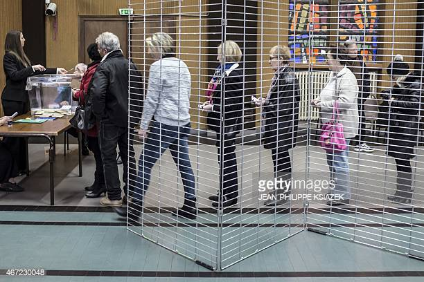 People wait in line to cast their ballots during the first round of the French departementales elections on March 22 2015 in Tullins central eastern...