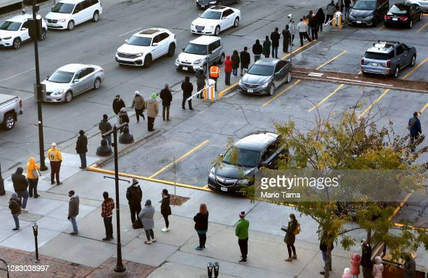 People wait in line to cast their ballots with social distance during early voting in the final days of the 2020 presidential election on October 30,...