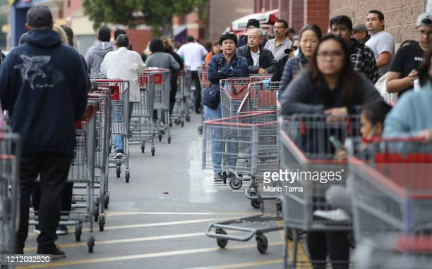 People wait in line to enter a Costco Wholesale store before it opened in the morning on March 12 2020 in Glendale California Once the store opened...