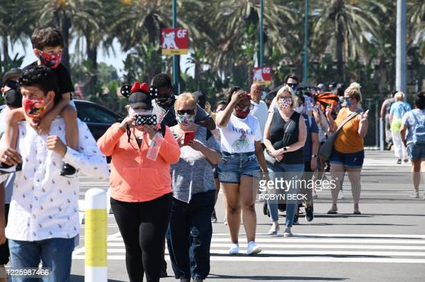 People wait in line to enter Downtown Disney in Anaheim, California on July 9 the first day the outdoor shopping and dining complex has been open to...