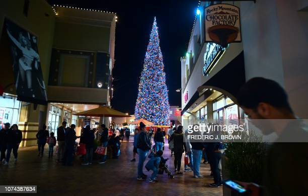 People wait in line to enter shops while shopping a week before Christmas on December 18 2018 at an outlet mall in Commerce California billing itself...