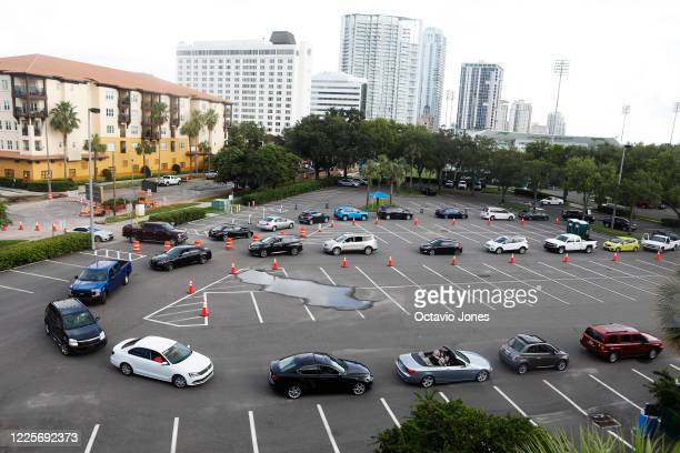 People wait in line to enter the COVID-19 drive-thru testing site at the Duke Energy for the Arts Mahaffey Theater on July 8, 2020 in St. Petersburg,...