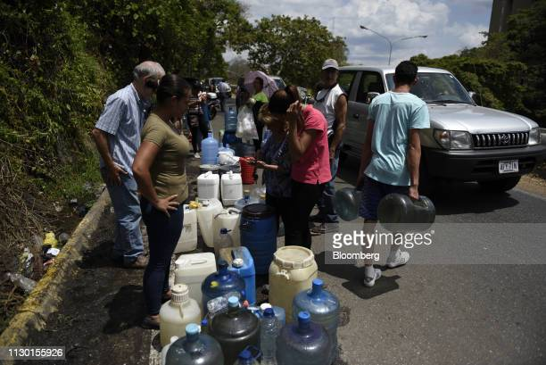 People wait in line to fill containers with water from a spring in Caracas Venezuela on Tuesday March 12 2019 President Nicolas Maduro speaking on...