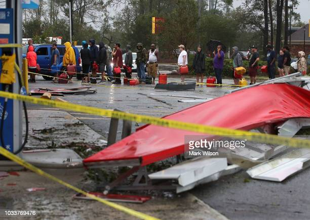 People wait in line to fill up their gas cans at a gas station that was damaged when Hurricane Florence hit the area on September 15 2018 in...