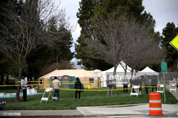 People wait in line to get a COVID19 test at a public testing station at a fire station on March 24 2020 in Hayward California Hundreds of people are...